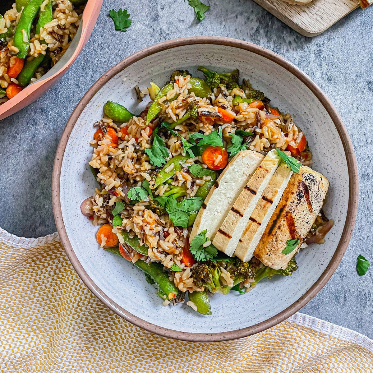 teriyaki forbidden wild rice bowl with grilled sliced tofu on top and in the background on marble cutting board