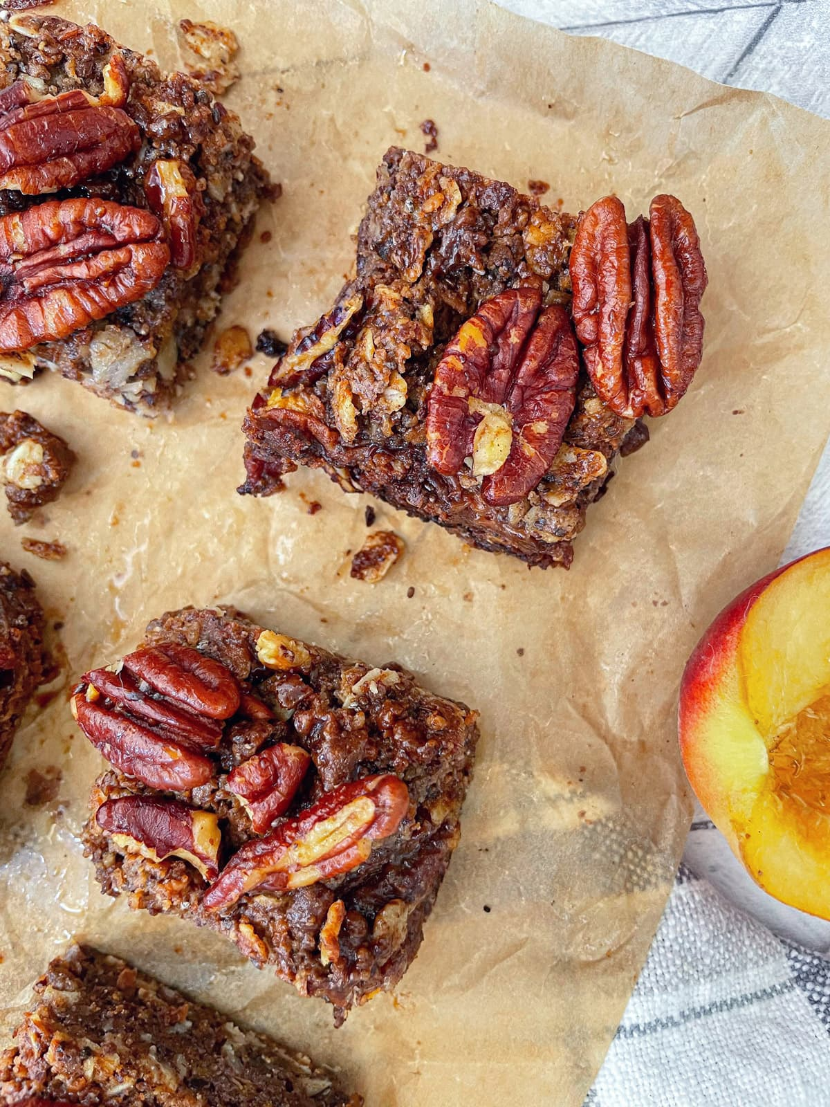 over head shot of Vegan Peach Crumble Bars with Candied Pecans with peach half on side