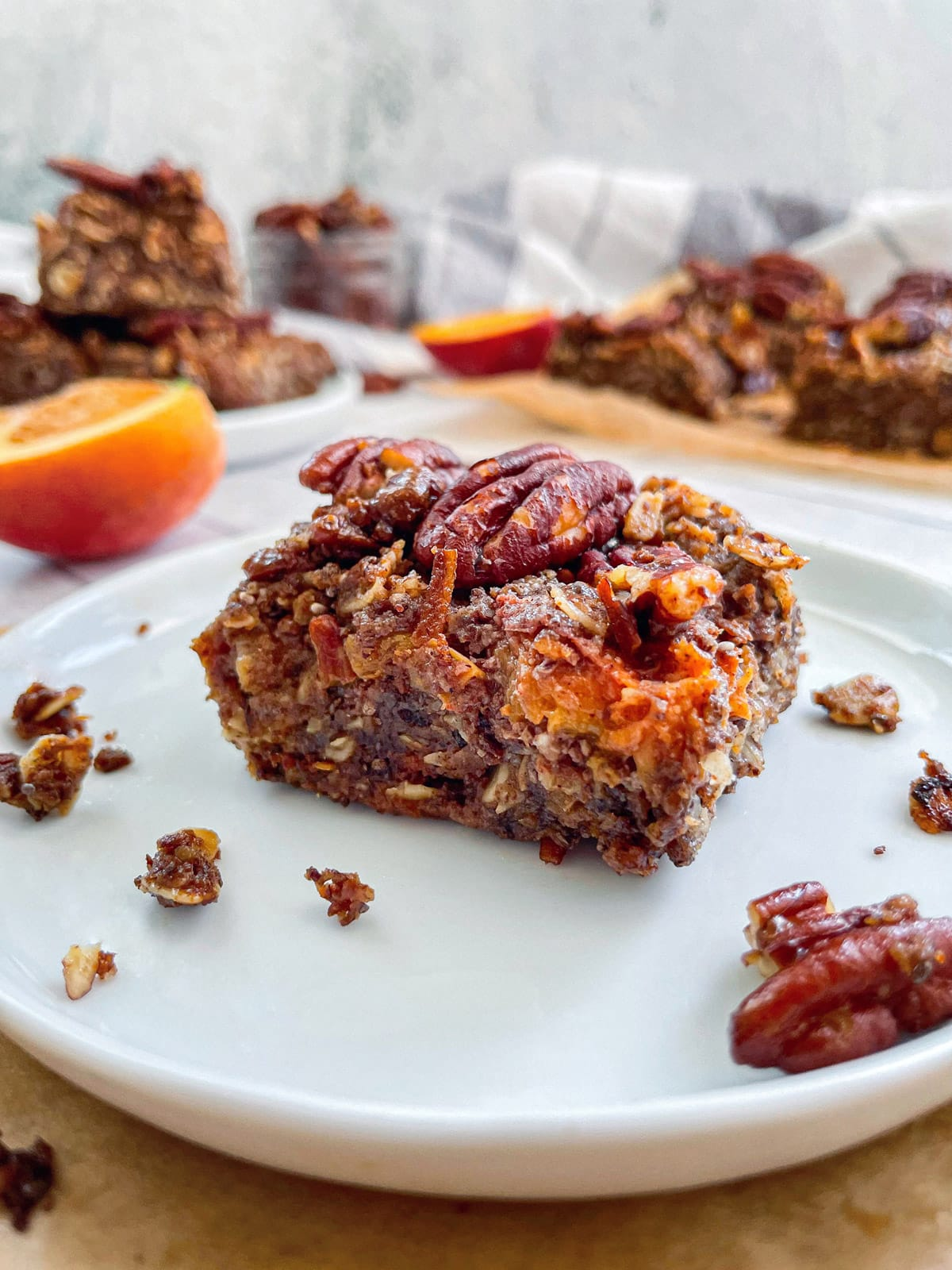 head on shot of one Vegan Peach Crumble Bar with Candied Pecans in a small white plate with other bars blurred in the background