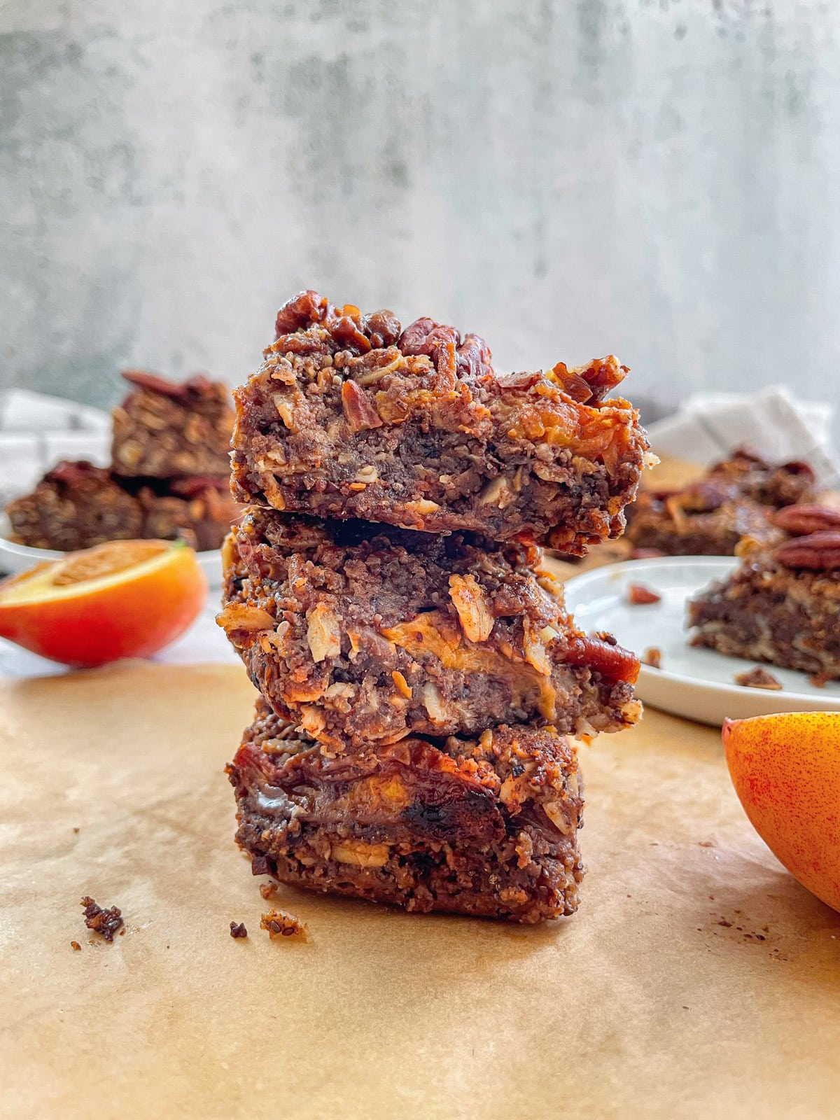3 Vegan Peach Crumble Bars with Candied Pecans stacked with other bars blurred in the background