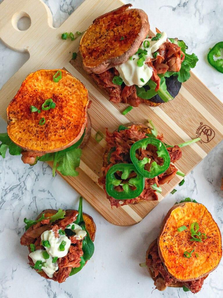 sweet potato vegan jackfruit pulled pork bbq sliders on cutting board with greens and avocado mayo