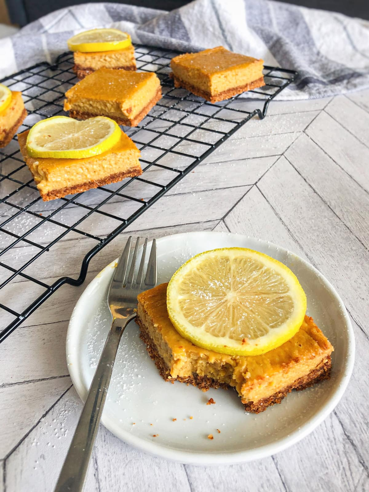 mango lemon shortbread bar in small white plate with lemon slice on top and bars on cooling rack in background